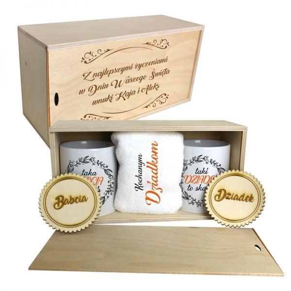 Zestaw kubków dla babci i dziadka z ecznikiem, podkładkami zapakowane w drewniane pudełko.